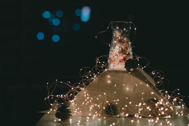 Weihnachtsdekoration. lichterketten und weihnachtsschmuck in einem glas mit warmen lichtern umgeben von einer lichterkette Premium Fotos