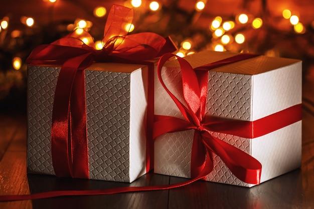 Weihnachtsdekoration mit geschenkboxen und lichtern Premium Fotos