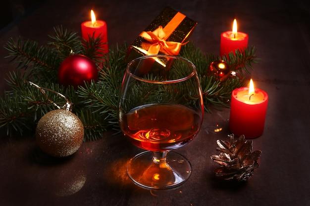 Weihnachtsdekoration mit glas kognak oder whisky, roten kerzen, geschenkbox und weihnachtsbaum. Premium Fotos