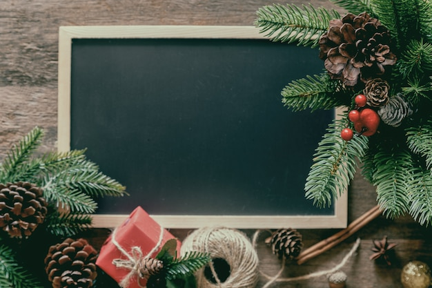 Weihnachtsdekoration mit tafel, kiefernblättern und kegeln, geschenkbox und stechpalmenbällen Premium Fotos