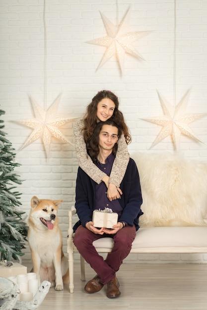 Weihnachtsdekorationen. junges küssendes und streichelndes glückliches paar beim sitzen auf einer bank nahe bei einem hund Premium Fotos