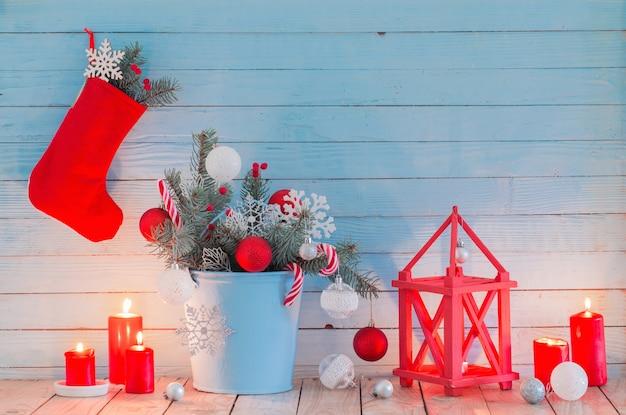 Weihnachtsdekorationen mit brennenden kerzen auf blauem hölzernem hintergrund Premium Fotos