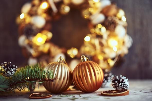 Weihnachtsdekorationen mit goldenen bällen und girlandenlichtern auf einem dunklen hintergrund Premium Fotos