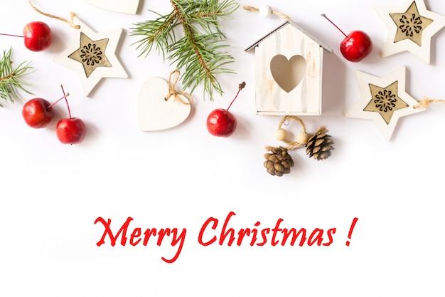 Weihnachtsdekorationen, tannenbaumaste, rote äpfel auf weißem hintergrund Premium Fotos