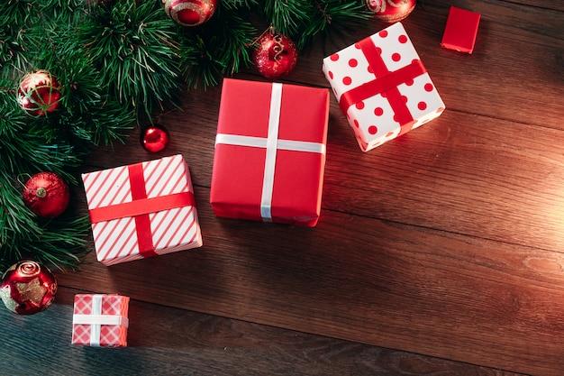 Weihnachtsdekorationen und geschenke, kiefernniederlassungen auf einem holztisch. feiertage weihnachten. copyspace. sicht von oben. Premium Fotos