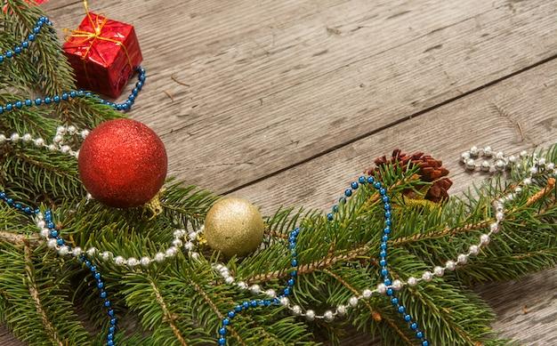 Weihnachtsdekorationsflitter mit niederlassungen des tannenbaums auf hölzernem hintergrund Premium Fotos