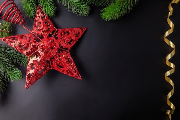 Weihnachtsdekorationsschwarzhintergrund mit rotem stern des treetop Premium Fotos
