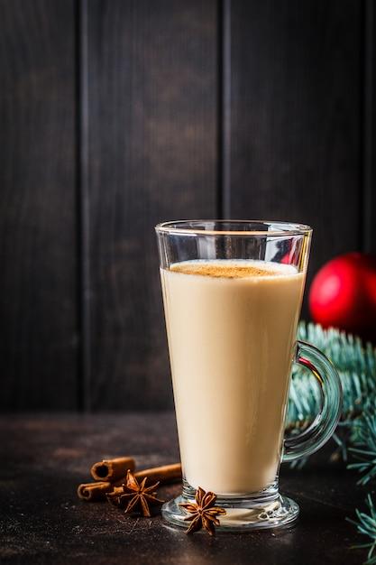 Weihnachtseierpunsch in einem glas im weihnachtshintergrund, kopienraum. Premium Fotos