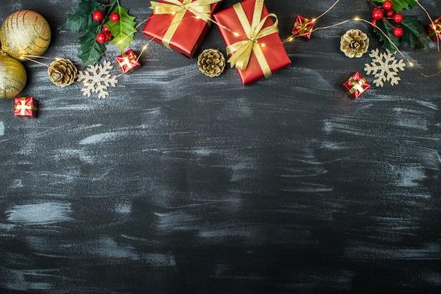 Weihnachtsfeiertagsrahmen mit weihnachtsbällen, geschenken, kiefernkegeln, mistel, schneeflocken und weihnachtslichtern auf einem strukturierten dunklen hintergrund Premium Fotos