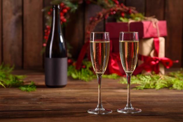 Weihnachtsfeiertagstabelle mit gläsern und eine flasche und geschenke Premium Fotos