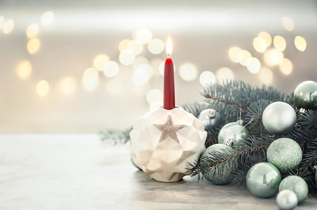 Weihnachtsfeiertagswand mit einer kerze in einem kerzenhalter. Kostenlose Fotos