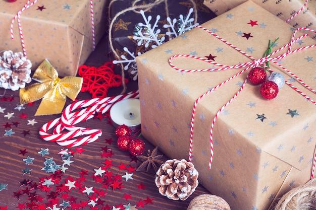 Weihnachtsferiengeschenkbox auf verzierter festlicher tabelle mit kiefernkegel-zuckerstangennüssen und schein spielt auf hölzernem hintergrund die hauptrolle Kostenlose Fotos