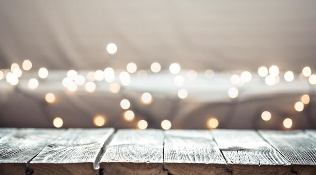 Weihnachtsferienwand mit leerer hölzerner tischplatte über festlichem bokehlicht verzieren. Kostenlose Fotos
