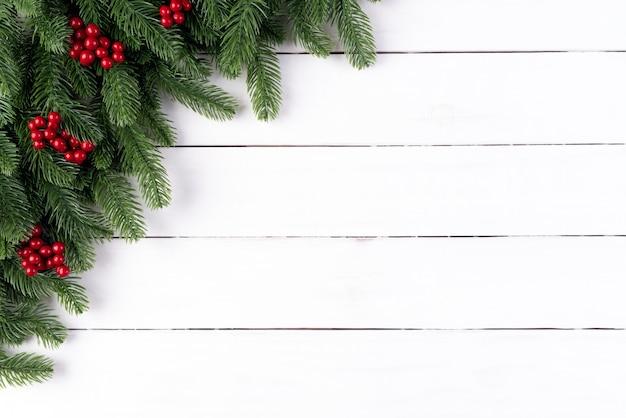 Weihnachtsfichtenzweige und rote beeren auf hölzernem hintergrund. Premium Fotos