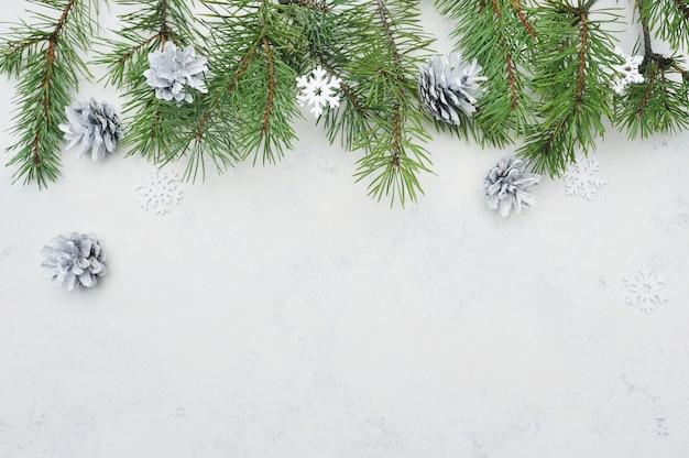 Weihnachtsflache lagegrußkarte mit tannenbaumasten und -schneeflocken Premium Fotos