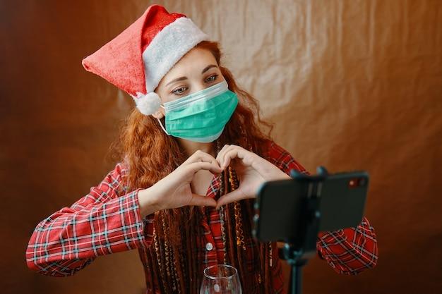 Weihnachtsfrau in der medizinischen maske, die online-videoanruf unter verwendung der smartphone-webcam mit den in form des herzens gefalteten händen tut. frau in weihnachtsmütze und kariertem pyjama. neujahrsurlaub in quarantäne. Premium Fotos