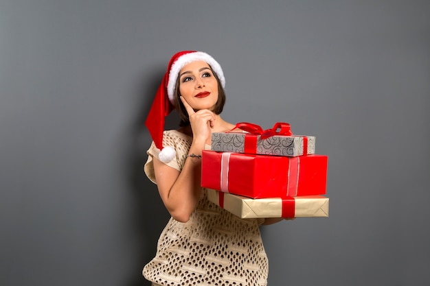 Weihnachtsfrau nachschlagen leere kopie raum halten geschenkbox geschenk, junge glückliche lächeln frau tragen weihnachtsmann hut, attraktive neujahr party mädchen, Premium Fotos