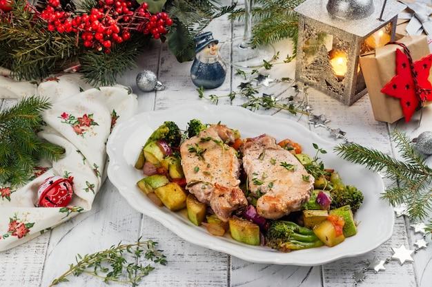 Weihnachtsgebratenes schweinefleisch mit gemüse Premium Fotos