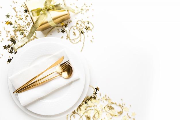 Weihnachtsgedeck mit dishware, goldenes tafelsilber auf weiß Premium Fotos