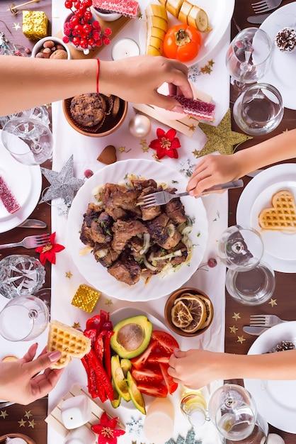 Weihnachtsgedeck mit lebensmittel auf einer platten-, mutter- und kinderhand, die lebensmittel und dekoration auf dunklem holztisch, ebenenlage übergibt Premium Fotos