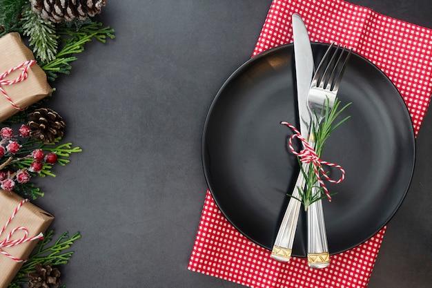 Weihnachtsgedeck mit schwarzblech, gabel und messer. Premium Fotos