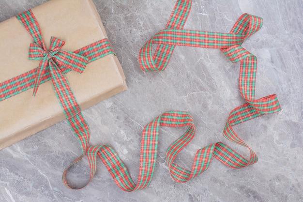 Weihnachtsgeschenk mit festlichem bogen auf marmorhintergrund. Kostenlose Fotos