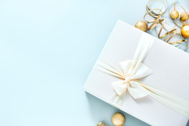 Weihnachtsgeschenk mit weißem bogen auf pastellhintergrund Premium Fotos