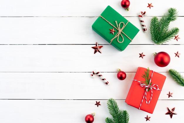 Weihnachtsgeschenkbox, fichtenzweige, rote kugel auf hölzernem hintergrund Premium Fotos