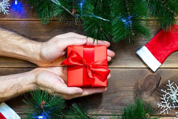 Weihnachtsgeschenkbox in den händen der männer auf den dekorationen des holztischs und des neuen jahres Premium Fotos