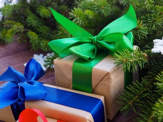 Weihnachtsgeschenkbox mit rotem band auf hölzernem, weihnachtsgeschenken mit dekorationen Premium Fotos