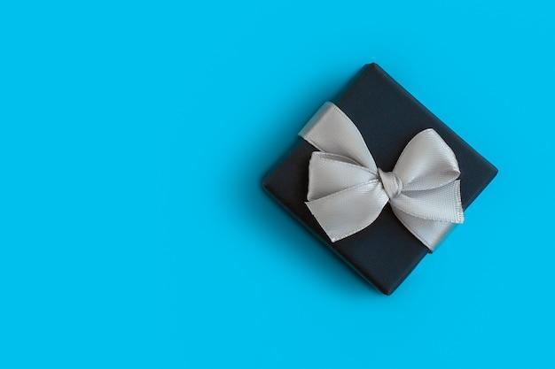 Weihnachtsgeschenkbox mit schleife auf blauem hintergrund, für modell oder entwurf, platz für copyspace Premium Fotos