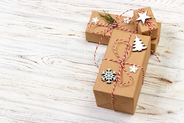 Weihnachtsgeschenkbox verziert durch schneeflocke auf hölzernem hintergrund Premium Fotos