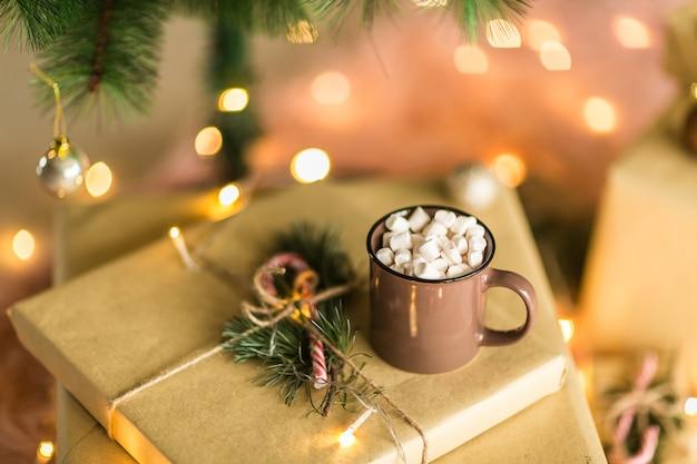 Weihnachtsgeschenkbox, zuckerstangen, schale heiße schokolade mit eibisch und tannenbaumaste Premium Fotos