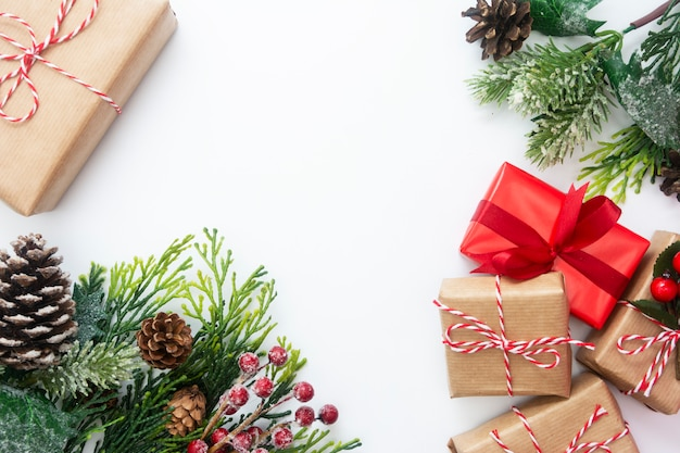 Weihnachtsgeschenkboxen, angeredete tannenzweige, kiefernkegel, weißer hintergrund. Premium Fotos