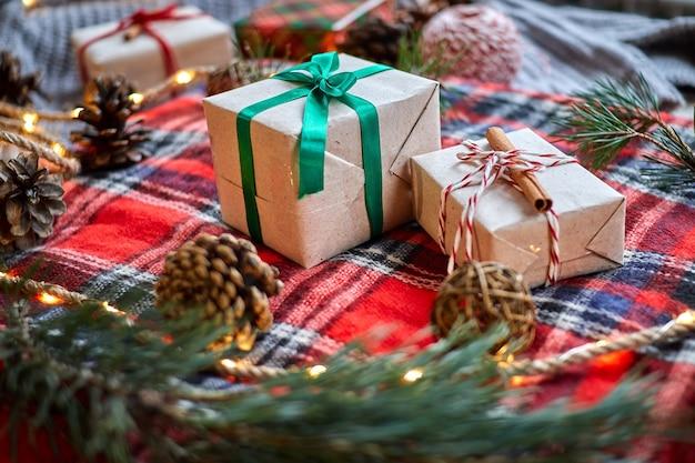 Weihnachtsgeschenke auf dem hintergrund eines roten karierten wollplaids mit girlanden von zapfen und tannenzweigen Premium Fotos