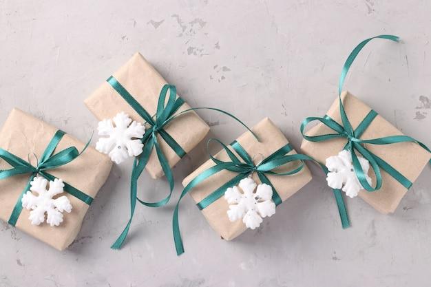 Weihnachtsgeschenke in kraftpapier mit grünen bändern auf grau Premium Fotos