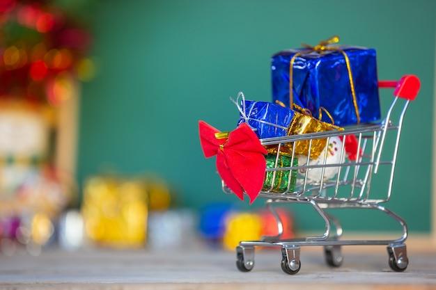 Weihnachtsgeschenkkästen in den verschiedenen farben gelegt in einen einkaufswagen Kostenlose Fotos