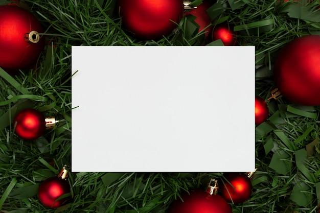Weihnachtsgirlande aus blättern und kugeln auf einem roten tisch Kostenlose Fotos