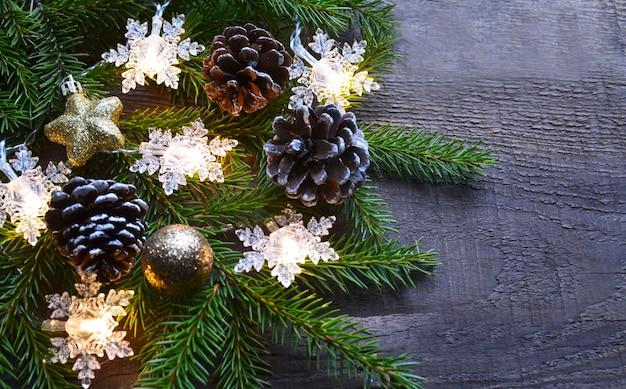 Weihnachtsgirlande lichter und tanne ast auf alten holztisch winter festliche dekoration Premium Fotos
