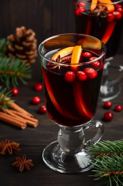 Weihnachtsglühwein mit orange und moosbeeren. feiertag verziert mit tannenzweigen und gewürzen. Premium Fotos