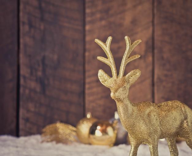 Weihnachtsgoldren-dekoration mit hölzernem hintergrund Premium Fotos