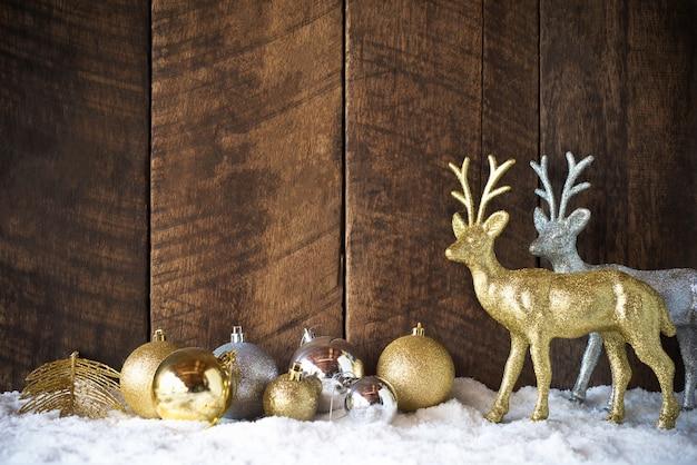 Weihnachtsgoldsilberne ball- und rendekoration mit hölzernem hintergrund Premium Fotos