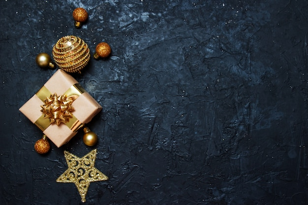 Weihnachtsgrußkarte zusammensetzung. geschenk mit goldener weihnachtsdekoration auf dunkelblauem hintergrund. Premium Fotos