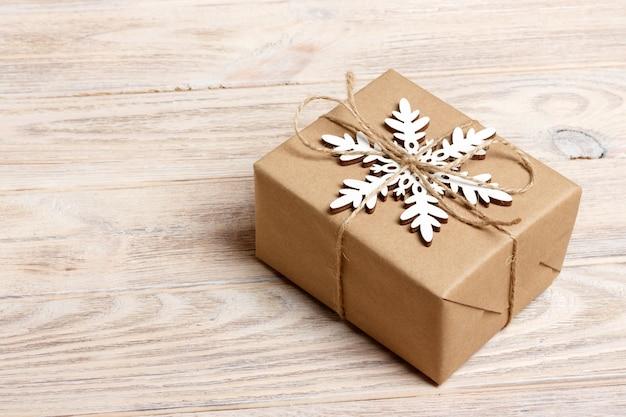 Weihnachtshandgemachte geschenkbox verziert mit kraftpapier und weißer schneeflocke auf draufsicht des weißen hölzernen hintergrundes. winter weihnachten urlaubsthema. frohes neues jahr. frohe weihnachten grußkarte Premium Fotos