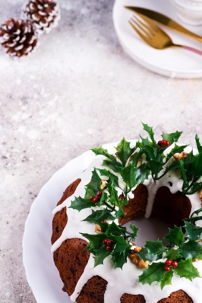 Weihnachtshausgemachter dunkler schokolade bundt kuchen verziert mit stechpalmenbeerenzweigen auf stein Premium Fotos