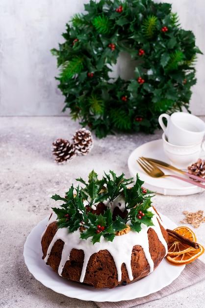 Weihnachtshausgemachter dunkler schokolade bundt kuchen verziert mit weißer zuckerglasur und stechpalmenbeerenniederlassungen auf einem leichtbeton Premium Fotos