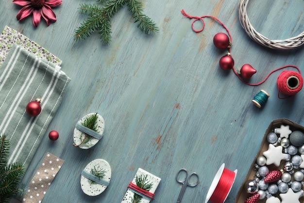 Weihnachtshintergrund auf geknistertem holz mit weihnachtsbaumtannenzweigen, geschenkboxen und dekorationen in rot, weiß und grün. Premium Fotos
