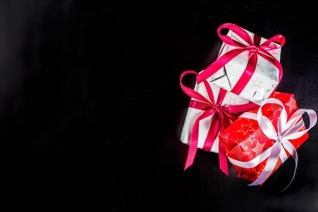 Weihnachtshintergrund für grußkarte, mit weihnachtsbaumast und geschenkboxen mit bändern, auf schwarzem draufsicht-kopienraum des hintergrundes für text Premium Fotos