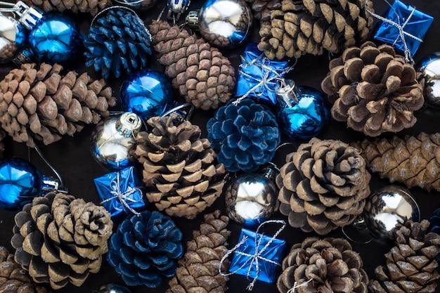 Weihnachtshintergrund mit blauen verzierungen und schneebedecktem tannenzapfen. weihnachtsfeierdekoration mit glänzenden kugeln. Premium Fotos
