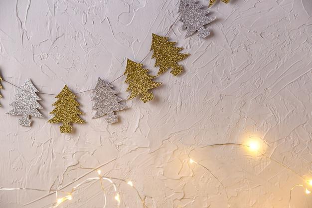 Weihnachtshintergrund mit feiertagssymbol von girlanden in form von weihnachtsbäumen Premium Fotos